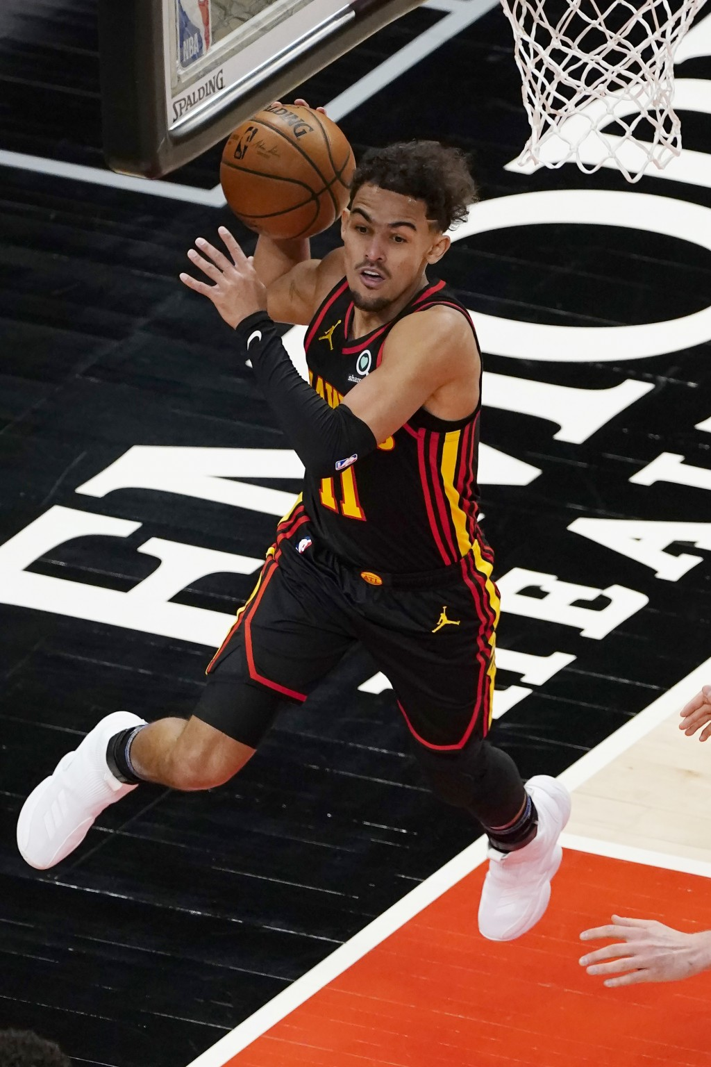 Atlanta Hawks guard Trae Young (11) keeps the ball in play during the first half of the team's NBA basketball game against the Denver Nuggets on Sunda...