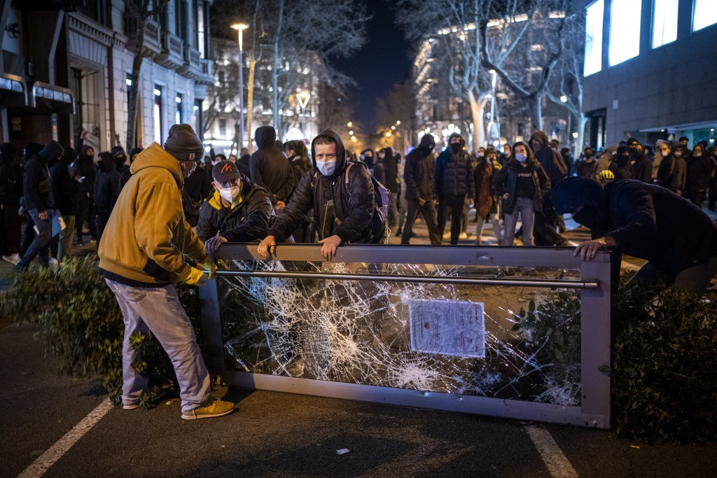 Demonstrators make barricades during clashes with police during a protest condemning the arrest of rap artist Pablo Hasél in Barcelona, Spain, Tuesday...