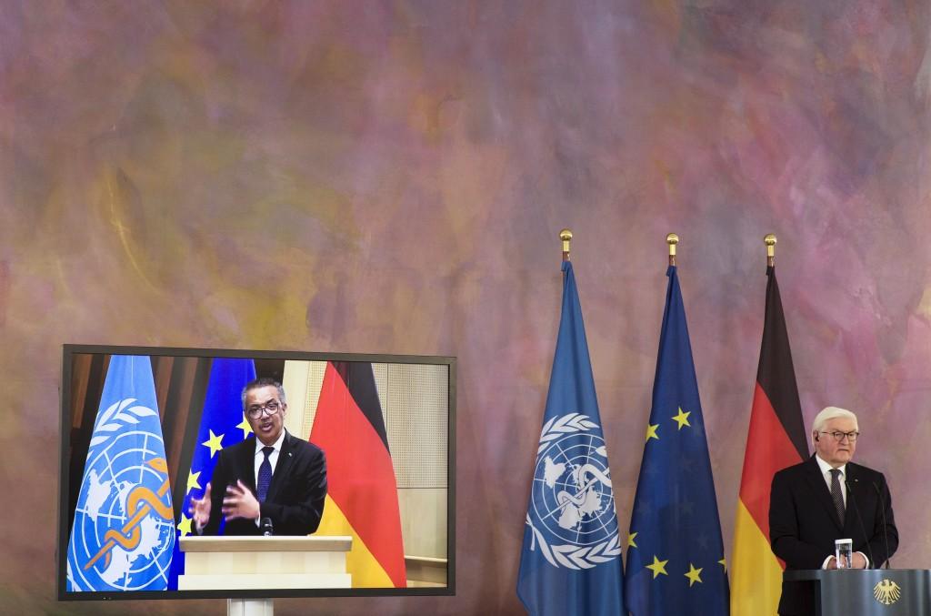 German President Frank-Walter Steinmeier, right, and Director General of the World Health Organization Tedros Adhanom Ghebreyesus, left on the screen,...