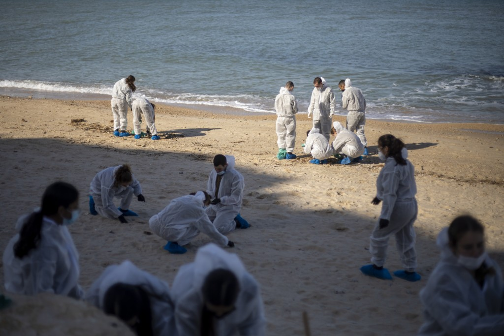 Israeli soldiers wearing protective suits clean tar from a beach after an oil spill in the Mediterranean Sea in Sharon Beach Nature Reserve, near Gaas...