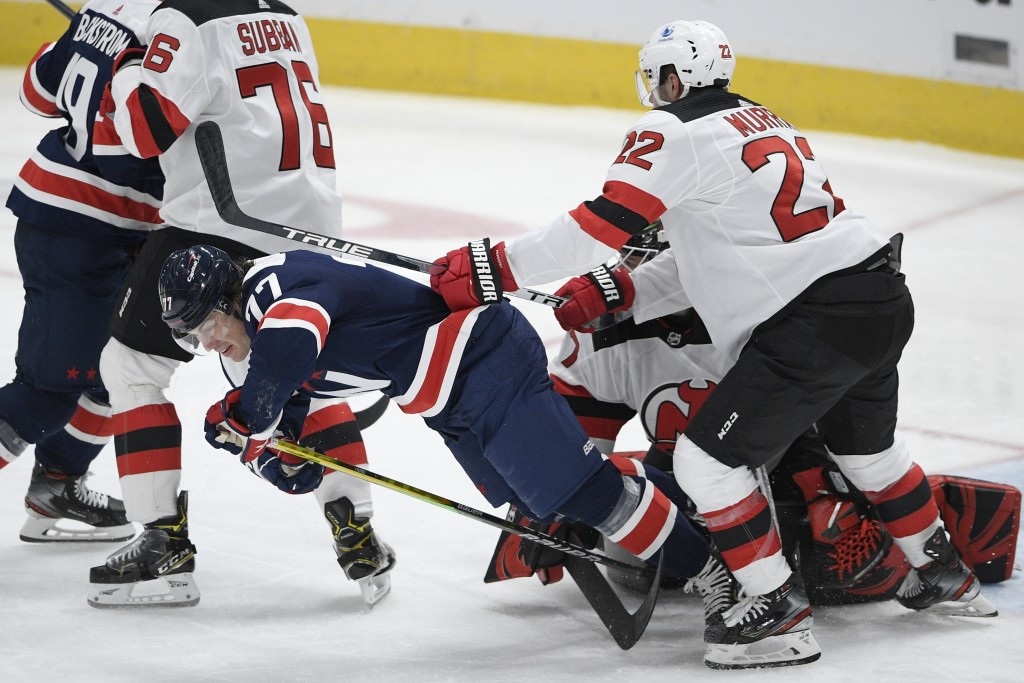 Washington Capitals right wing T.J. Oshie (77) falls to the ice next to New Jersey Devils defenseman Ryan Murray (22) during the second period of an N...