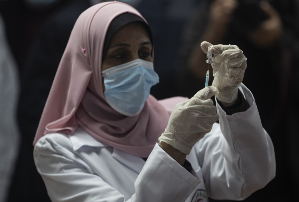 A Palestinian medic prepares a shot of the Russian-made Sputnik V coronavirus vaccine, in Gaza City, Monday, Feb. 22, 2021. (AP Photo/Khalil Hamra)