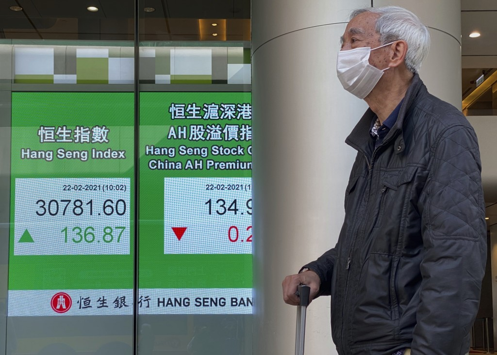 A man walks past a bank's electronic board showing the Hong Kong share index in Hong Kong Monday, Feb. 22, 2021. Asian shares were mixed on Monday as ...