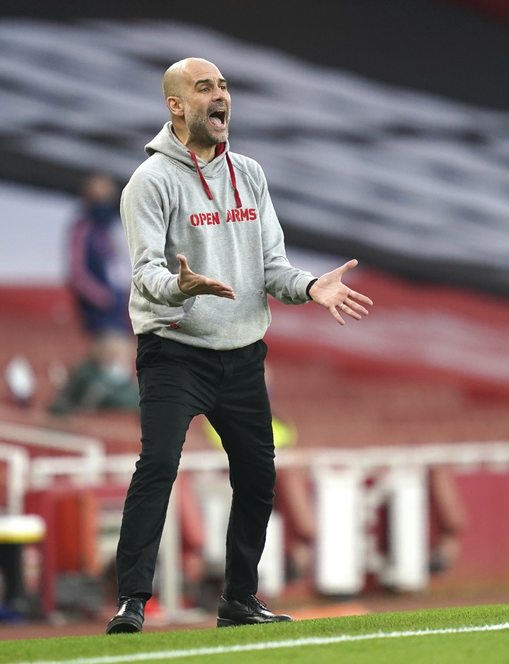 Manchester City's head coach Pep Guardiola reacts during the English Premier League soccer match between Arsenal and Manchester City at the Emirates s...