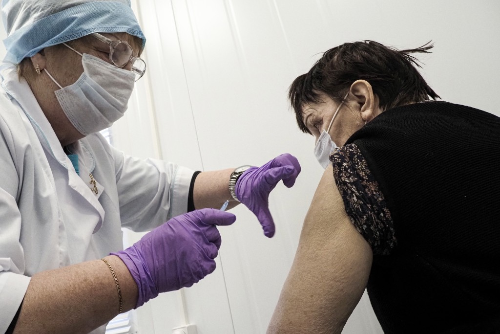 A Russian medical worker administers a shot of Russia's Sputnik V coronavirus vaccine to 75-year-old Maria Piparinen in a local rural medical post in ...