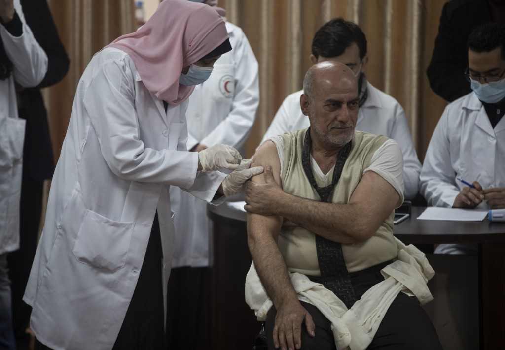 Former Palestinian Health Minister Jawad al-Tibi receives a shot of the COVID-19 Russian-made Sputnik V vaccine, in Gaza City, Monday, Feb. 22, 2021. ...