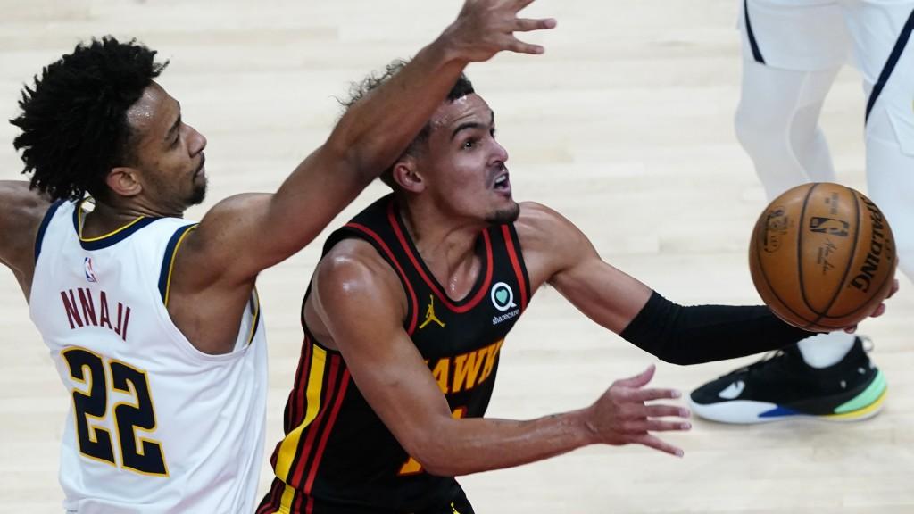 Atlanta Hawks guard Trae Young (11) goes past Denver Nuggets forward Zeke Nnaji (22) to score during the second half of an NBA basketball game Sunday,...