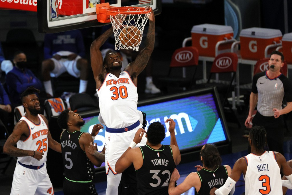 Julius Randle, center, of the New York Knicks dunks as Malik Beasley, left, and Karl-Anthony Towns, right, of the Minnesota Timberwolves look on durin...