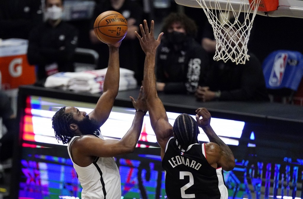 Brooklyn Nets guard James Harden, left, shoots as Los Angeles Clippers forward Kawhi Leonard defends during the first half of an NBA basketball game S...