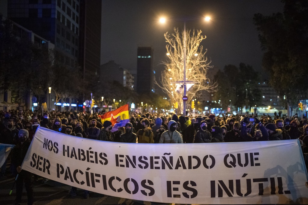 """Demonstrators march holding a banner reading """"you have taught us that being peaceful is useless"""" during a protest condemning the arrest of rap artist ..."""