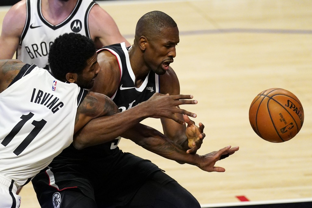 Brooklyn Nets guard Kyrie Irving, left, and Los Angeles Clippers center Serge Ibaka go after a rebound during the first half of an NBA basketball game...