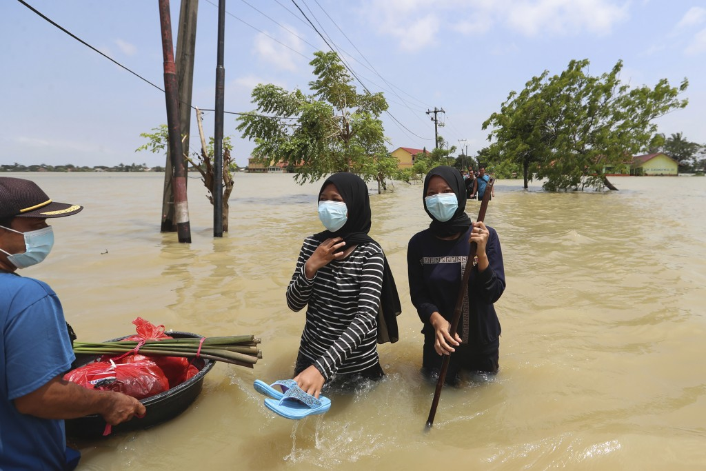 Indonesian men carry their belongings as they wade through the water at a flooded neighborhood following heavy rains in Bekasi, Indonesia, Monday, Feb...