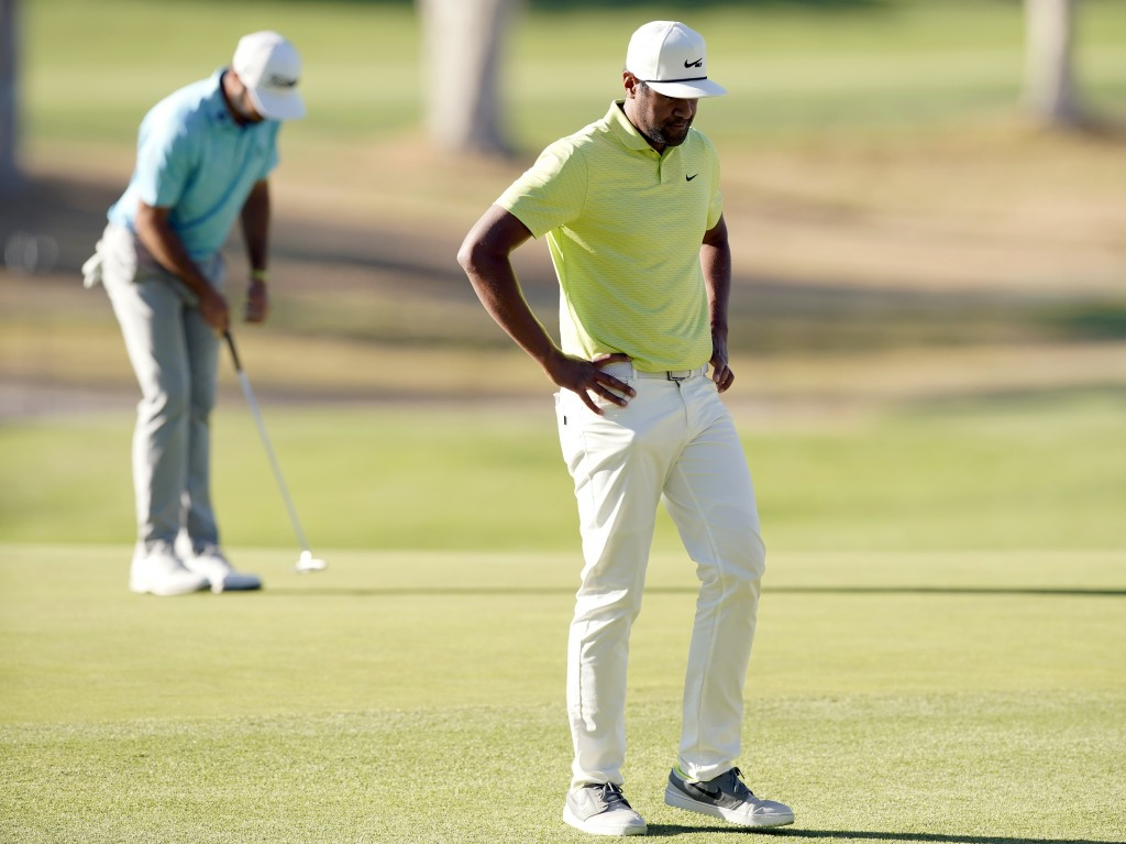 Tony Finau, right, reacts after missing a putt on the 10th green as Max Homa putts, back left, during the first playoff hole in the final round of the...
