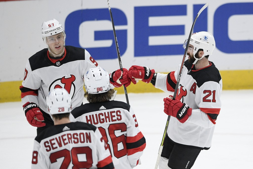 New Jersey Devils left wing Nikita Gusev (97) celebrates his goal with right wing Kyle Palmieri (21), center Jack Hughes (86) and defenseman Damon Sev...