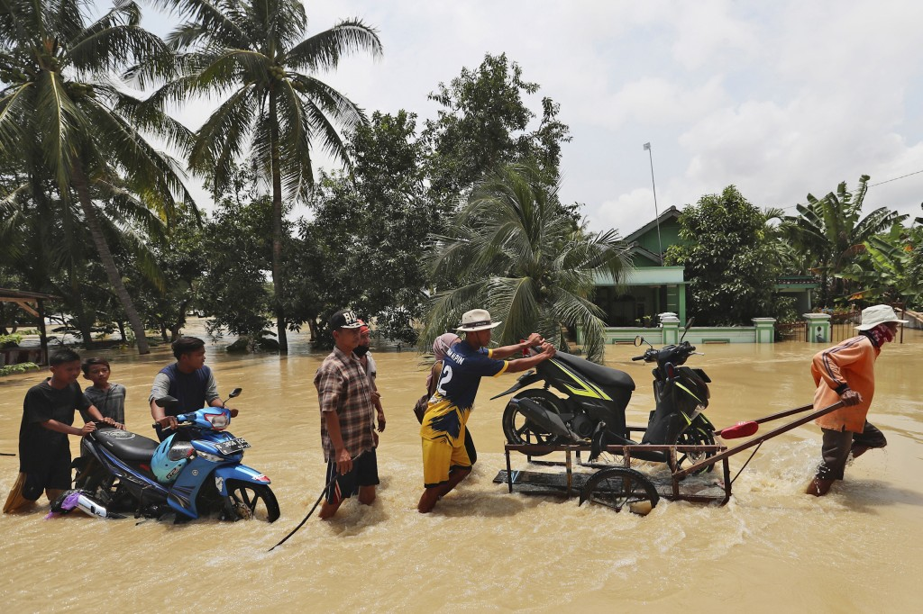 People push their motorcycles through an area flooded after the embankment of Citarum River burst, in Bekasi, Indonesia, Monday, Feb. 22, 2021. Heavy ...
