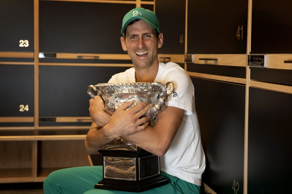 Serbia's Novak Djokovic embraces the Norman Brooks Challenge Cup in the locker room after defeating Russia's Daniil Medvedev in the men's singles fina...