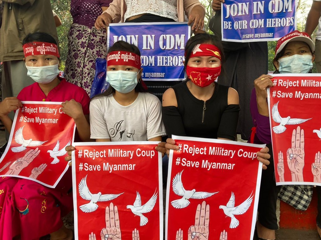 """Anti-coup protesters hold posters that read """"#Reject Military Coup #Save Myanmar"""" as they gather under an elevated roadway just outside the Hledan Cen..."""
