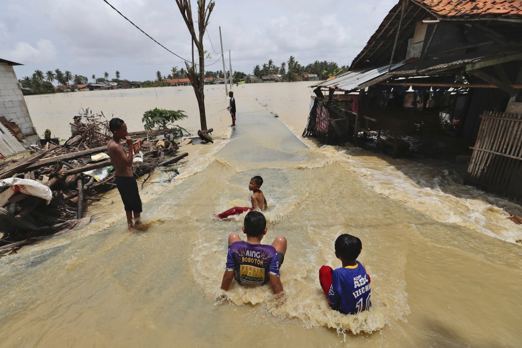 Children play in the water at a neighborhood flooded after the Citarum River embankment in Bekasi, Indonesia, Monday, Feb. 22, 2021. Thousands of resi...