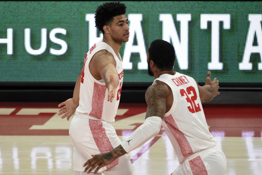 Houston guard Quentin Grimes, left, celebrates his three point basket with Reggie Chaney during the first half of an NCAA college basketball game agai...