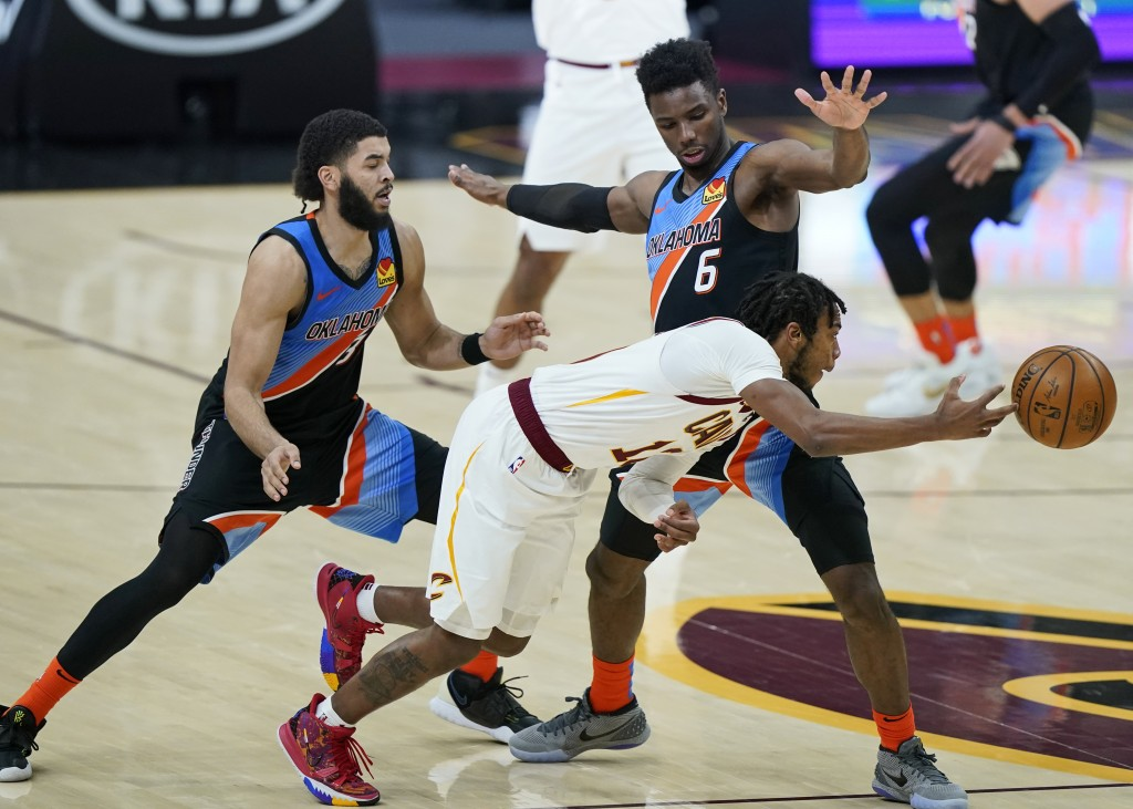 Cleveland Cavaliers' Darius Garland, front, passes against Oklahoma City Thunder's Hamidou Diallo, right, as Kenrich Williams, left, defends in the se...