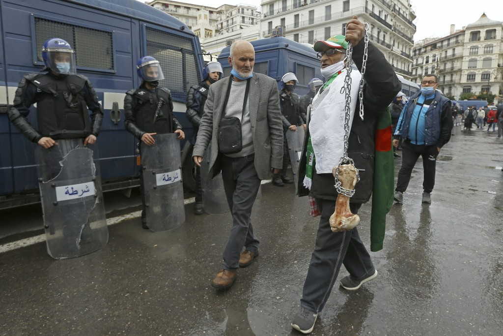 "A man holds a bone while shouting ""That's what's left for those who vote for the President"" as Algerians demonstrate in Algiers to mark the second ann..."