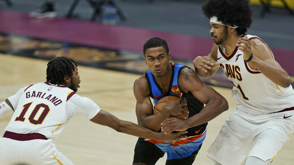 Oklahoma City Thunder's Theo Maledon, center, drives between Cleveland Cavaliers' Darius Garland, left, and Jarrett Allen in the second half of an NBA...