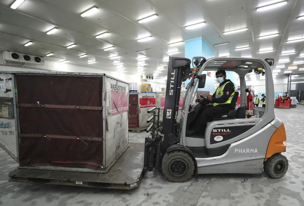 A Pfizer-BioNTech COVID-19 coronavirus vaccine shipment is offloaded into a refrigerated storage space at Dubai International Airport cargo terminal, ...