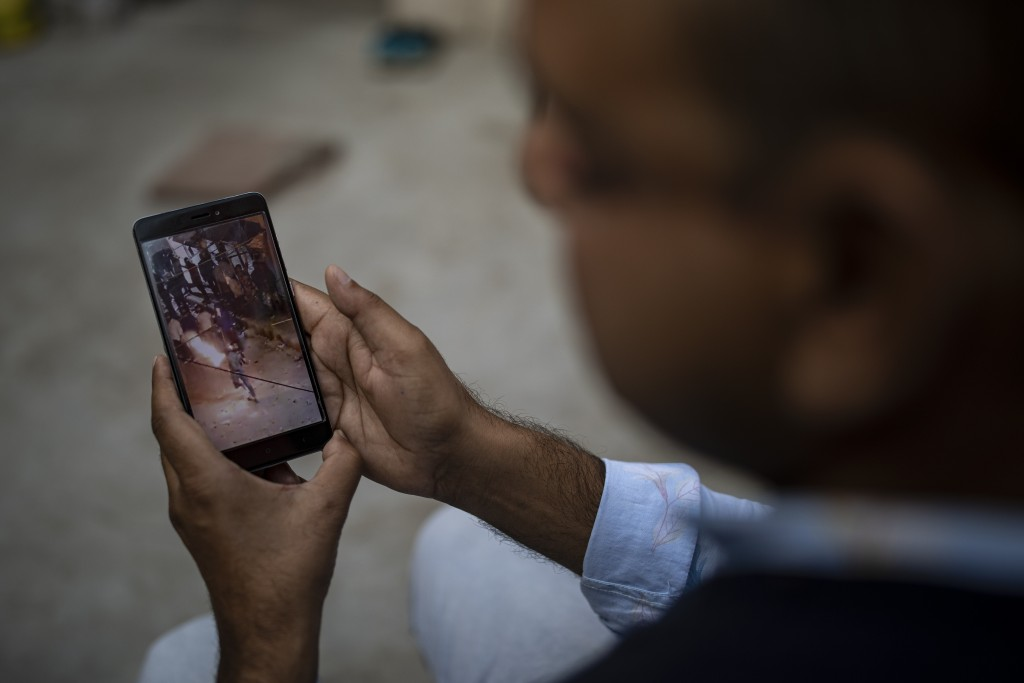 Muhammad Nasir Khan, who was shot by a Hindu mob during the February 2020 communal riots, watches a video showing a Hindu mob throwing petrol bomb tow...