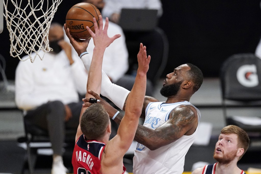 Los Angeles Lakers forward LeBron James, center, shoots as Washington Wizards center Moritz Wagner, left defends along with forward Davis Bertans duri...