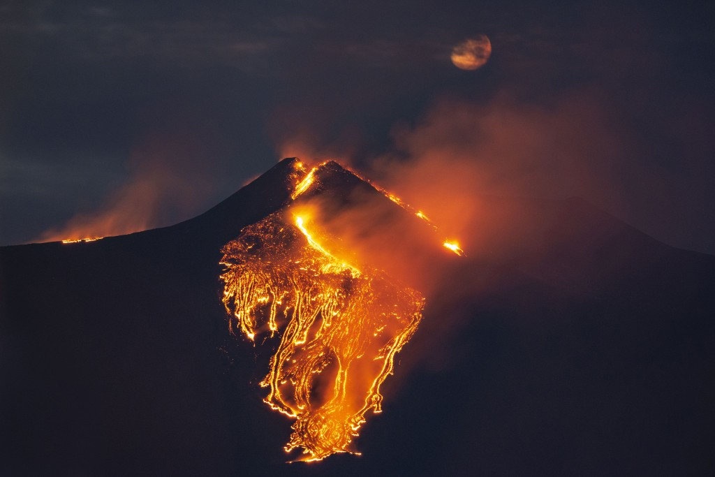 The moon is partially seen in the sky as lava flows from the Mt Etna volcano, near Catania in Sicily, southern Italy, early Tuesday, Feb. 23 , 2021. T...