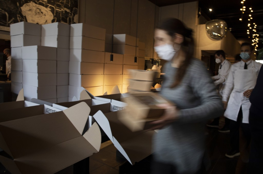 FILE - In this Saturday, Nov. 7, 2020 file photo, a restaurant staff member carries dinner boxes as she prepares part of nearly 600 take-away orders a...