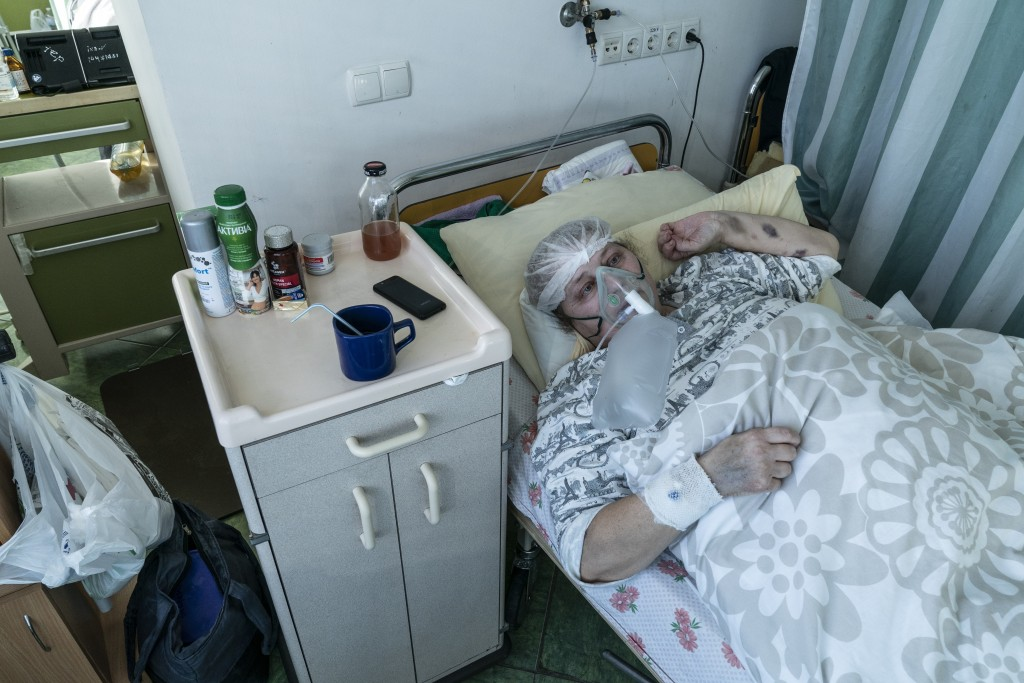 An elderly woman suffering from COVID-19 breathes with the help of an oxygen mask in central district hospital of Kolomyia, western Ukraine, Tuesday, ...