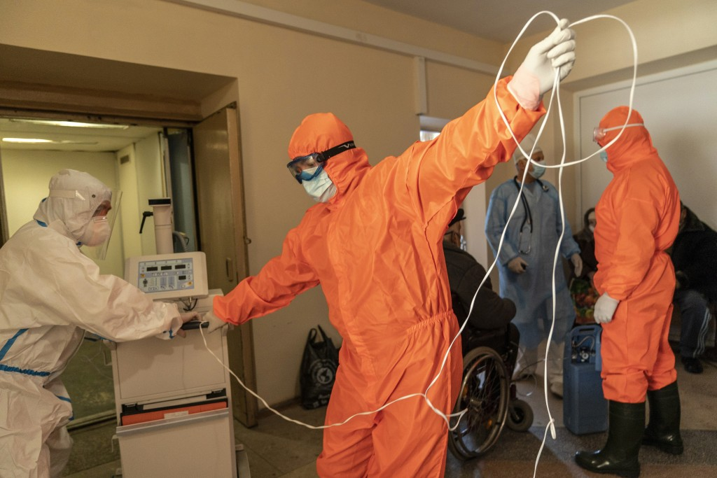 Medical workers wearing special suits to protect against coronavirus setup a medical equipment for a patient in a hospital in Kolomyia, western Ukrain...