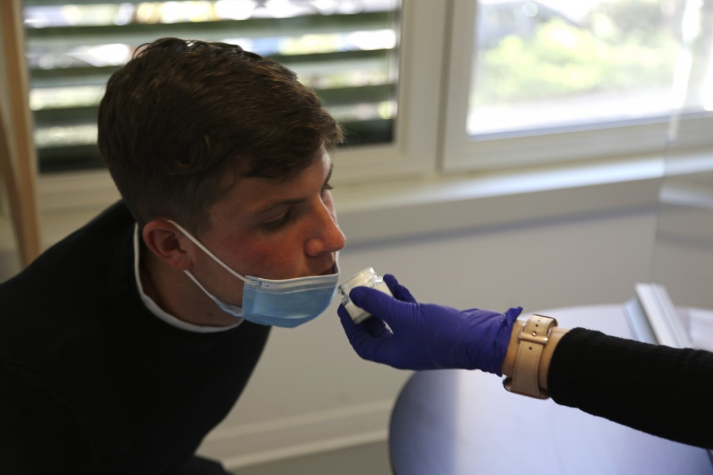 Evan Cesa, a patient, smells a small pot of fragrance during tests in a clinic in Nice, France, on Monday, Feb. 8, 2021, to help determine how his sen...