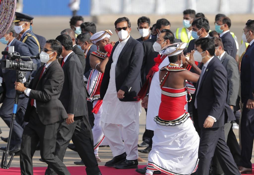 Pakistan's Prime Minister Imran Khan, center, walks with Sri Lankan Prime Minister Mahinda Rajapaksa upon his arrival in Colombo, Sri Lanka, Tuesday, ...