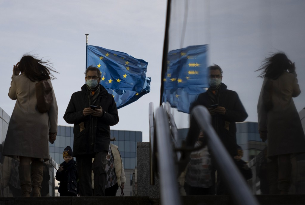 Flags of the European Union flap in the wind as people walk with protective face masks near a set of stairs in front of EU headquarters in Brussels, T...