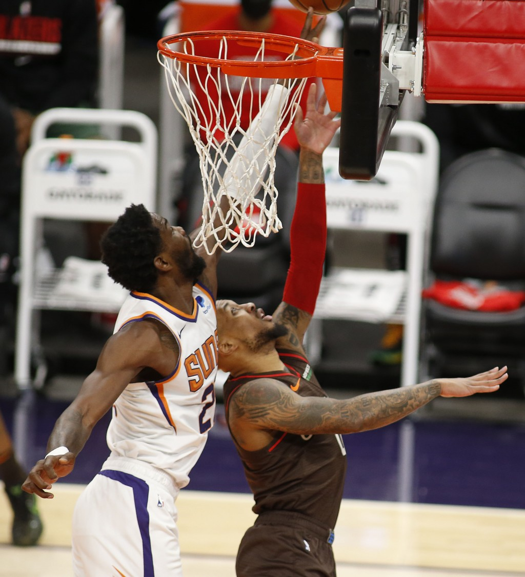 Phoenix Suns' Deandre Ayton blocks the shot of Portland Trail Blazers Damian Lillard during the first half of an NBA basketball game Monday, Feb. 22, ...