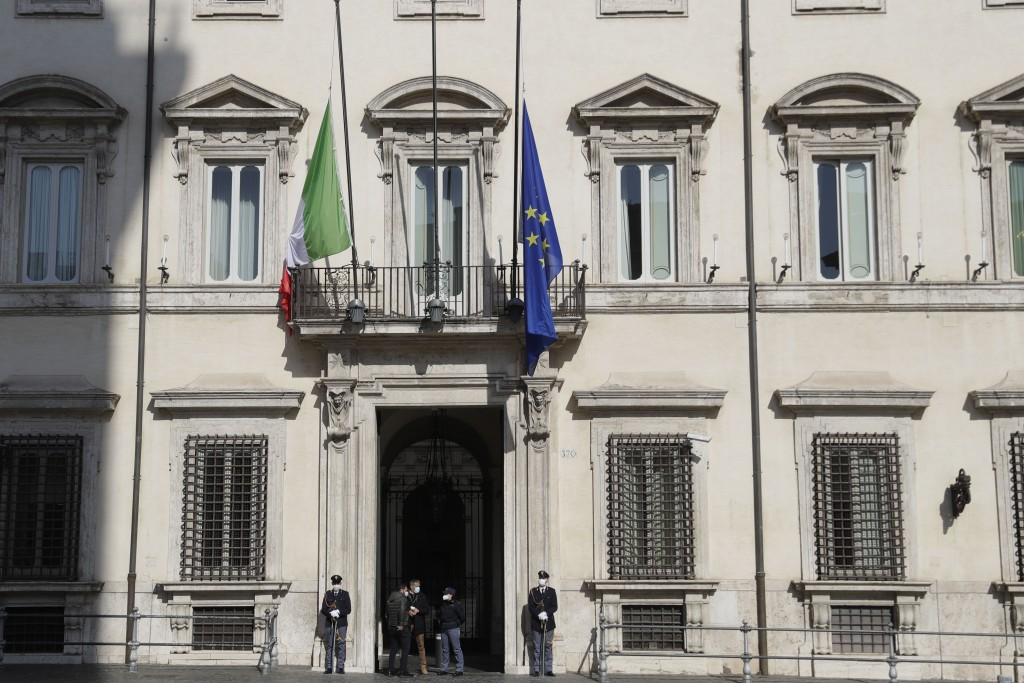 The flags of Italy and the EU, right fly at half mast outside Chigi palace, Premeir's office in Rome, Tuesday, Feb. 23, 2021. The Italian ambassador t...