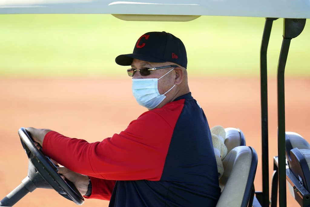 Cleveland Indians manager Terry Francona wears a face covering as he drives around on a golf cart during a spring training baseball practice Monday, F...