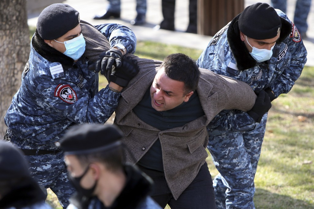 Police detain an opposition demonstrator during an anti-government protest at the government building in Yerevan, Armenia, Tuesday, Feb. 23, 2021. Sev...