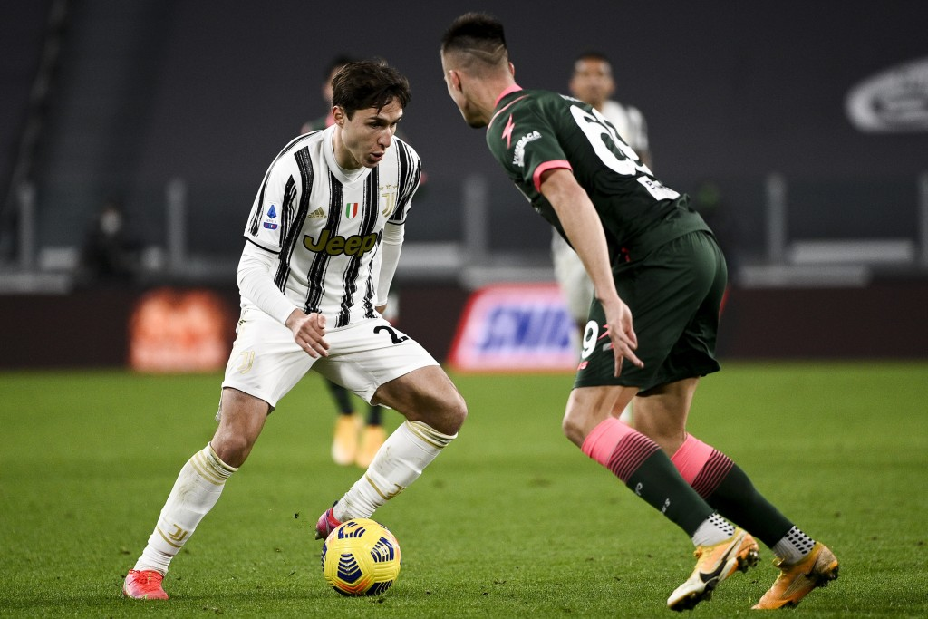 Juventus' Federico Chiesa, left, battles for the ball with Crotone's Arkadiusz Reca during the Serie A soccer match between Juventus and Crotone, at t...