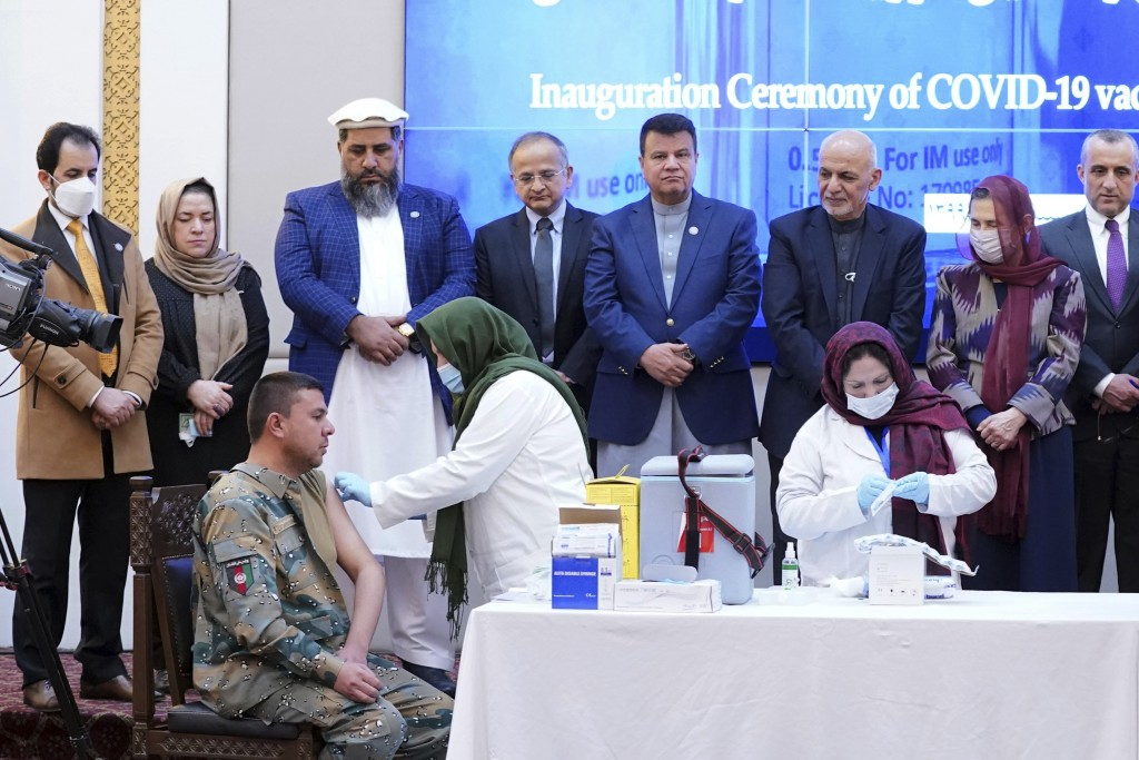 An Afghan security personnel, left, receives Indian's AstraZeneca coronavirus vaccine from health officials at the Afghan presidential palace in Kabul...