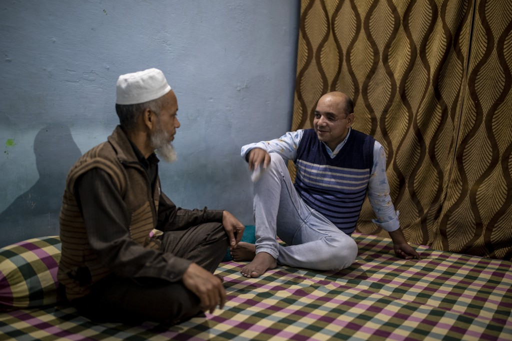Muhammad Nasir Khan, right,who was shot by a Hindu mob during the February 2020 communal riots, speaks to his father Abdul Jaleel inside his home  in ...