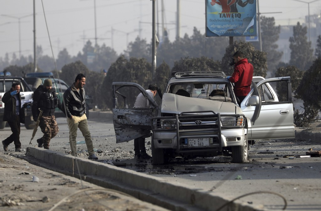 FILE - In this Feb. 2, 2021 file photo, security personnel inspect the site of a bomb attack in Kabul, Afghanistan. The U.N. says the number of civili...
