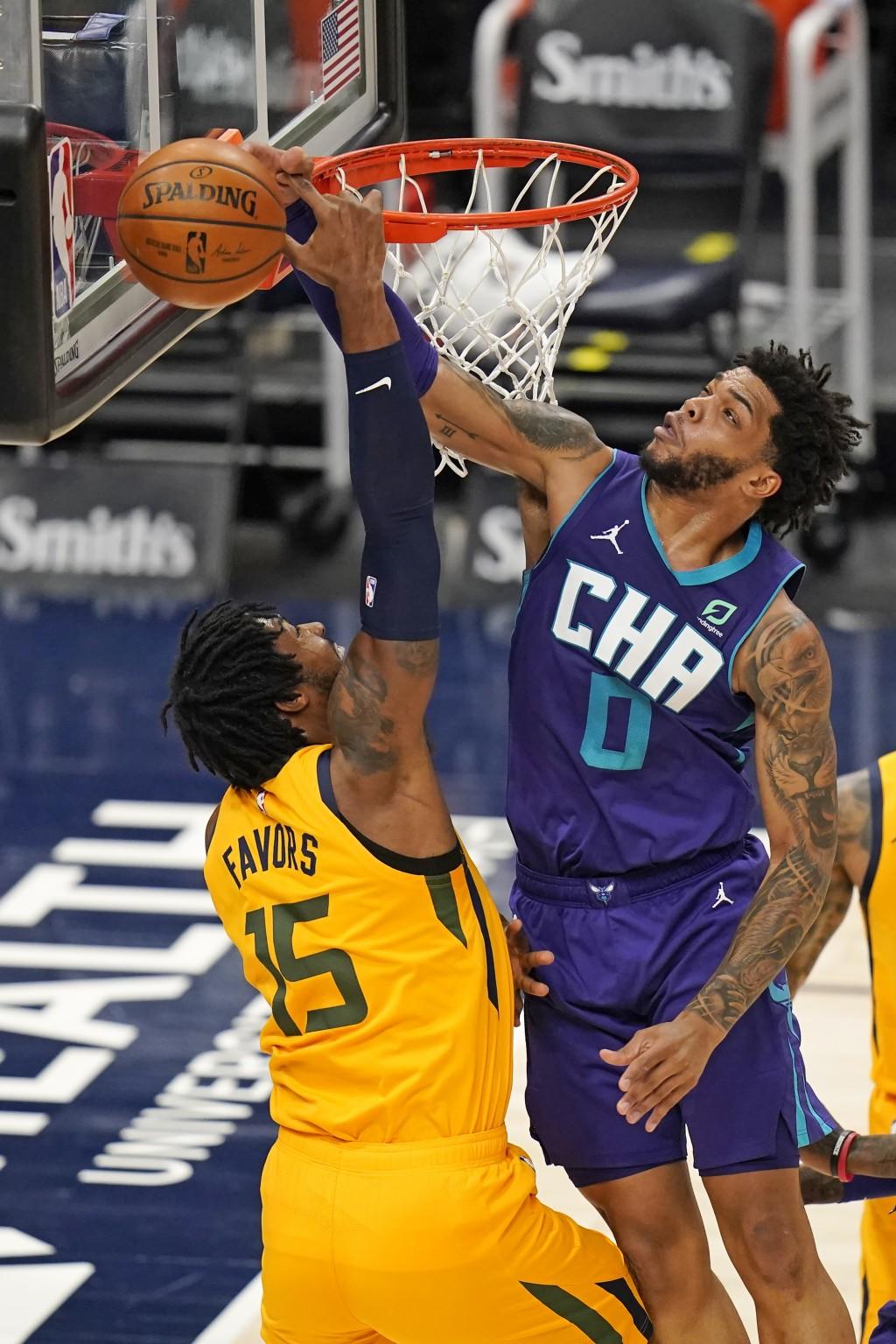Charlotte Hornets forward Miles Bridges (0) blocks the shot from Utah Jazz center Derrick Favors (15) in the first half during an NBA basketball game ...