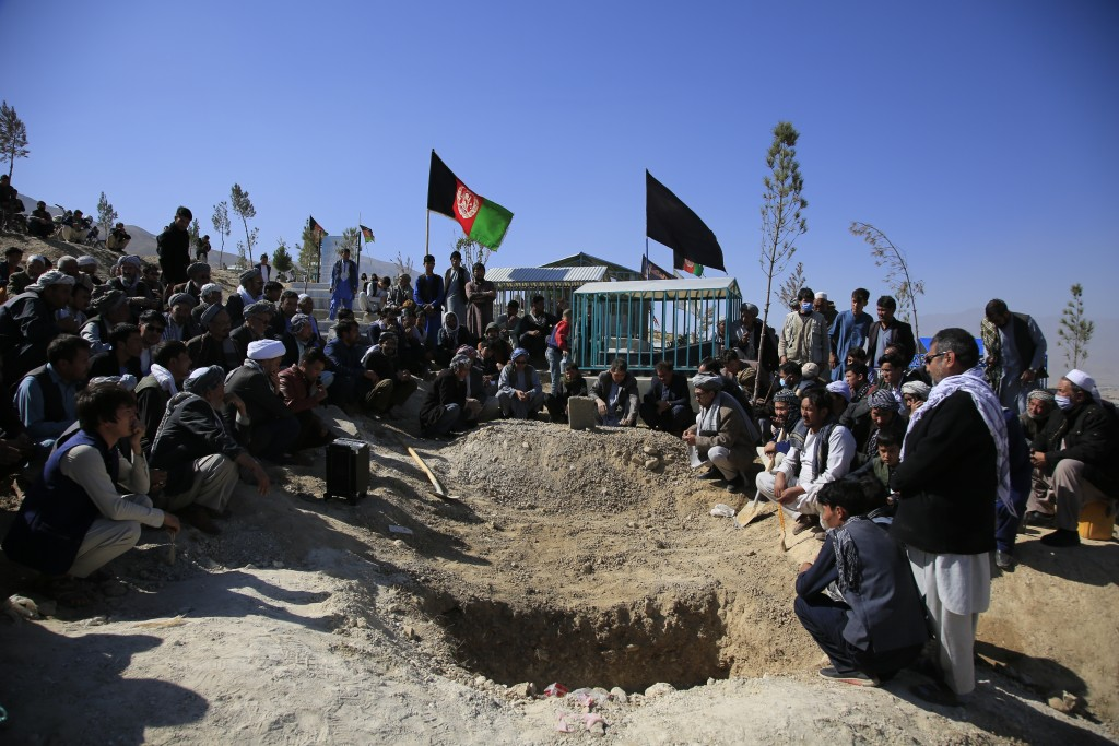 FILE - in this Oct. 25, 2020 file photo, Afghan men bury a victim of a suicide attack that targeted an education center, in Kabul Afghanistan. The U.N...