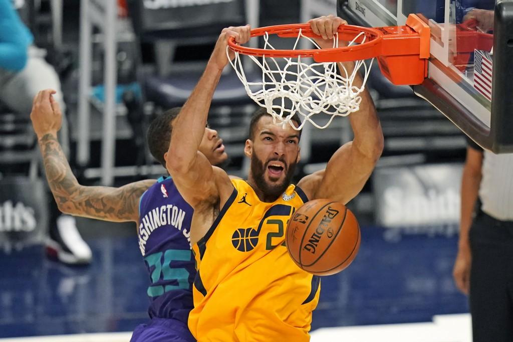 Utah Jazz center Rudy Gobert, right, dunks on Charlotte Hornets forward P.J. Washington (25) in the second half during an NBA basketball game Monday, ...