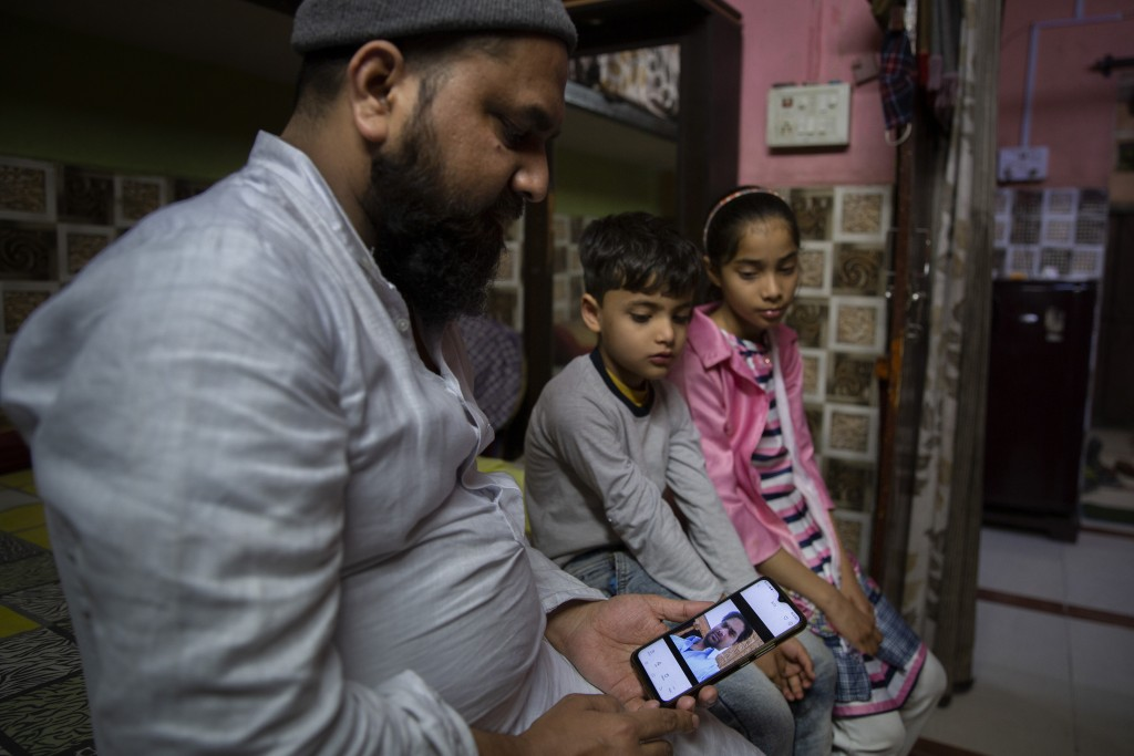 Haroon, holds a mobile phone as his nephew and niece look at the photograph of their father who was shot and killed by their Hindu neighbors during Fe...