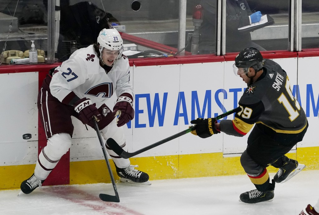 Vegas Golden Knights right wing Reilly Smith, right, passes the puck as Colorado Avalanche defenseman Ryan Graves covers in the first period of an NHL...