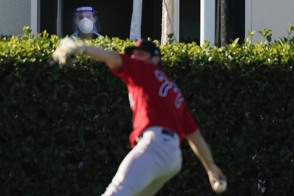 Boston Red Sox pitcher Jay Groome (77) throws the ball as a medical worker with a face shield near a testing site watches the players during spring tr...